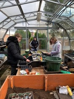 Pupils working at the school greenhouse